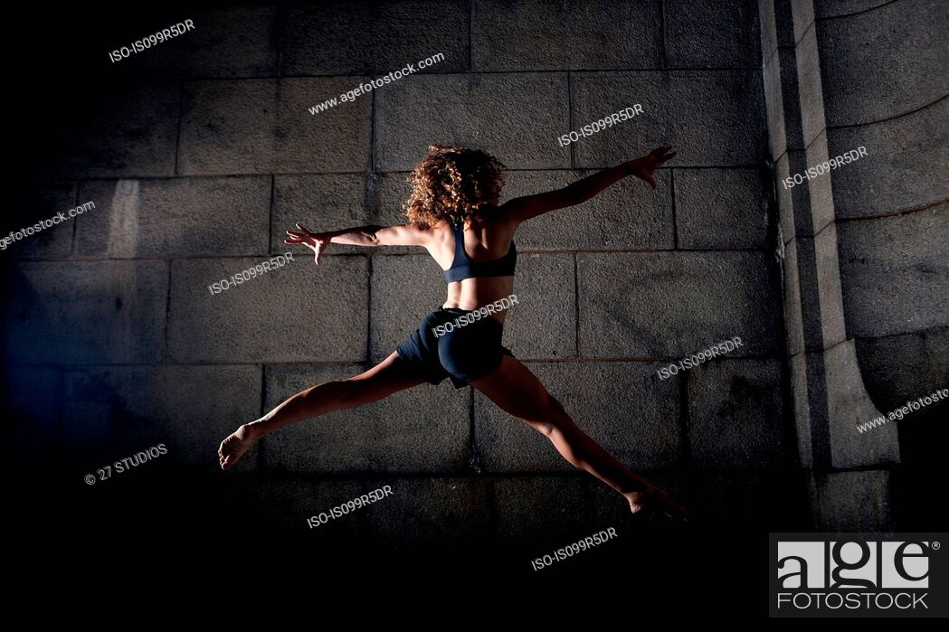 Stock Photo: Woman jumping with legs and arms open.