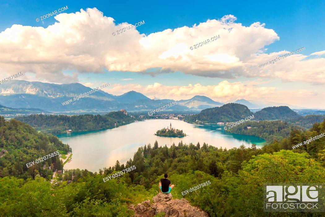 Stock Photo: Male traveler enjoying beautiful panoramic view of Julian Alps, Lake Bled with St. Marys Church of the Assumption on the small island, Bled, Slovenia, Europe.