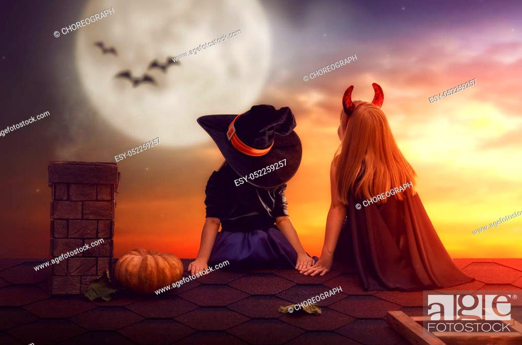 Stock Photo: Two happy sisters on Halloween. Funny kids in carnival costumes sitting on the roof. Cheerful children looking at moon.