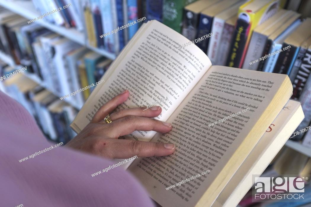 Stock Photo: Choosing a book in Library, UK.