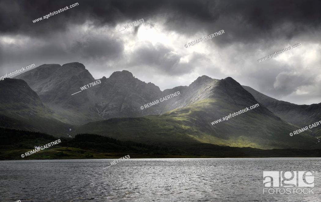 Stock Photo: White house under Blaven mountains of Black Cuillin Hills with sun rays under dark clouds at Loch Slapin Isle of Skye Scotland UK.