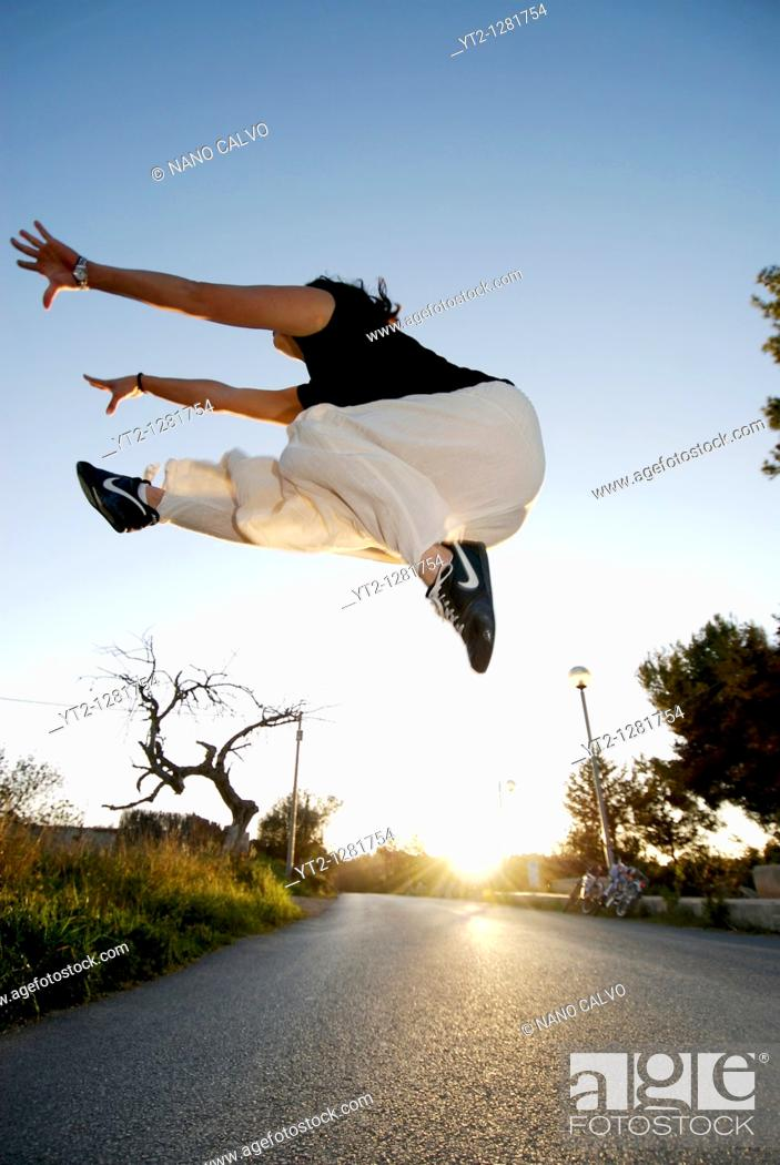 Stock Photo: Former artistic gymnast, Anabel Cheng, performing jumps and acrobatic movements in the street.