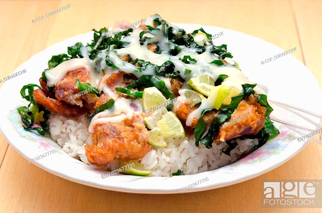 Stock Photo: Fried chicken with lemon sauce and herb over rice (famous thai food).