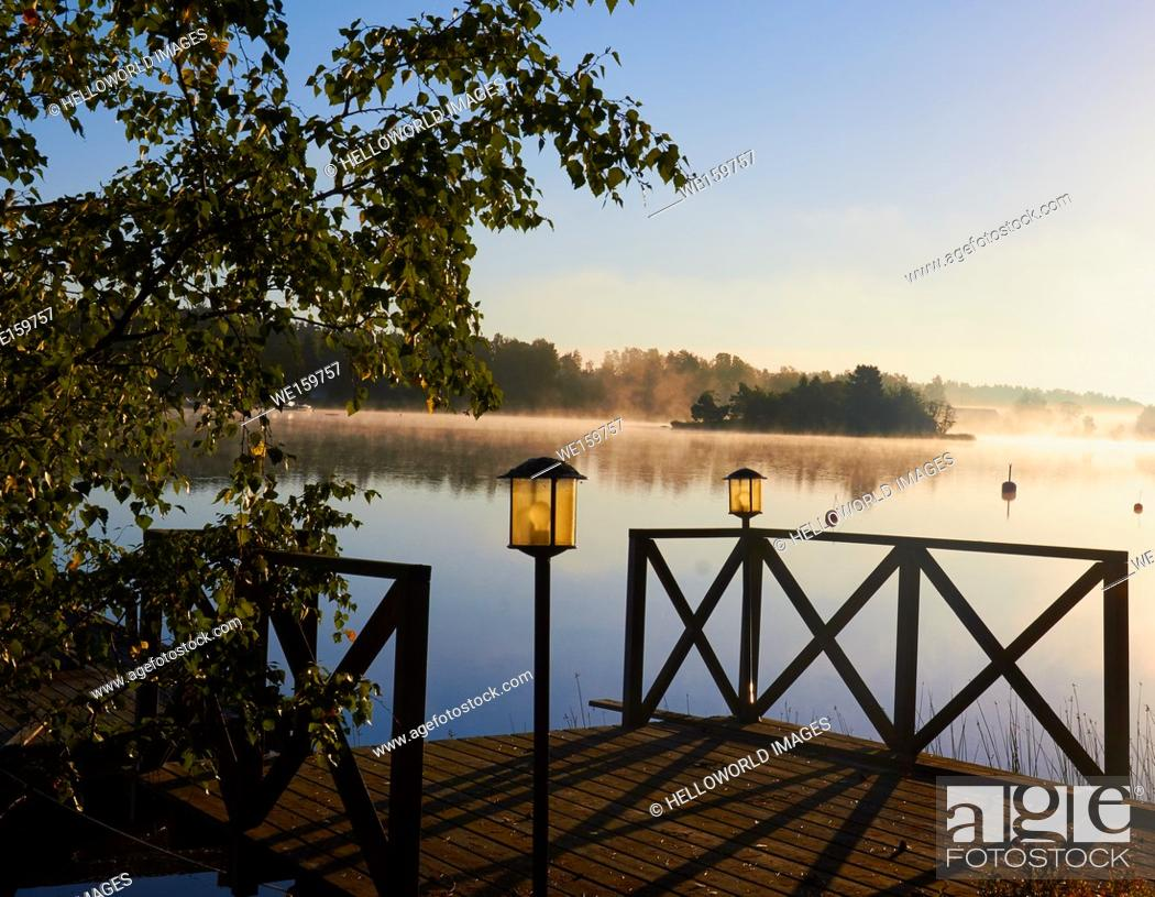 Photo de stock: Wooden lakeside platform on misty summer morning, Ljustero, Stockholm County, Sweden, Scandinavia. . Ljustero is an island in the northern part of the Stockholm.