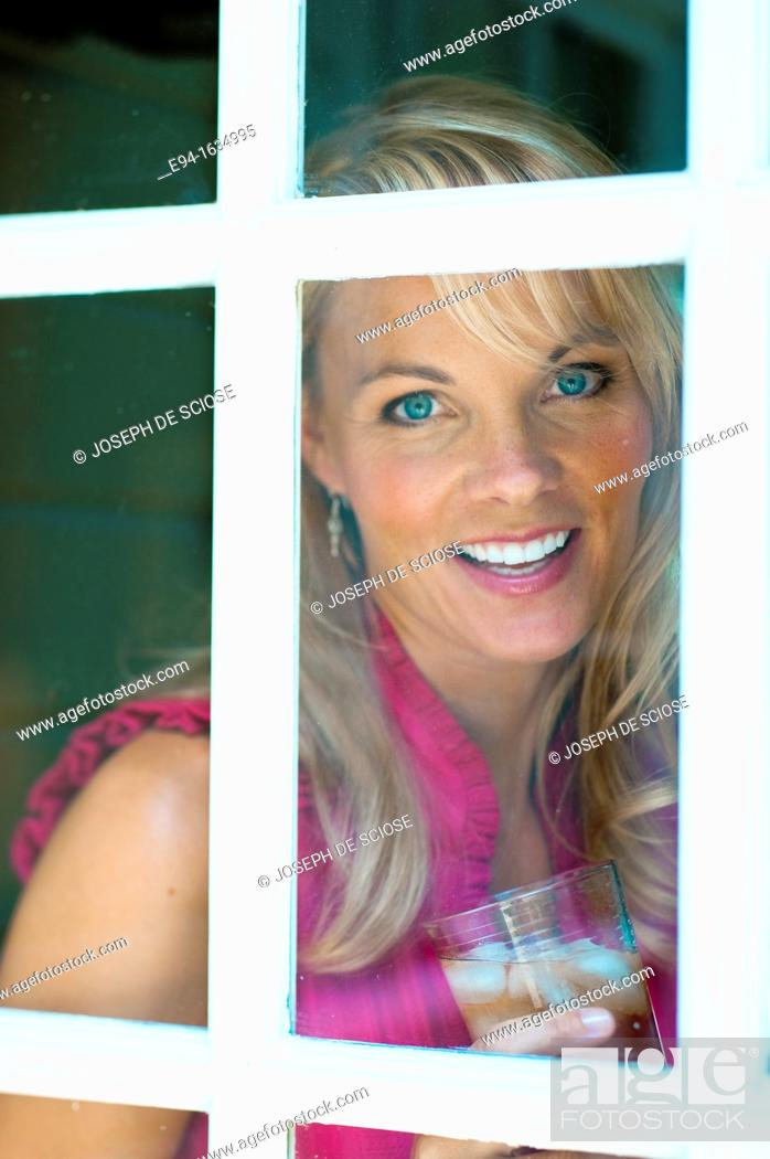 Stock Photo: 35 year old blond woman standing in a kitchen holding a glass of iced tea looking through a window at the camera.
