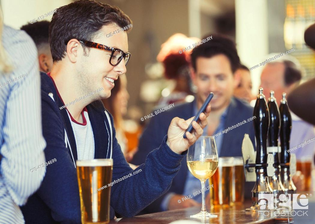 Stock Photo: Smiling man texting with cell phone drinking wine at bar.