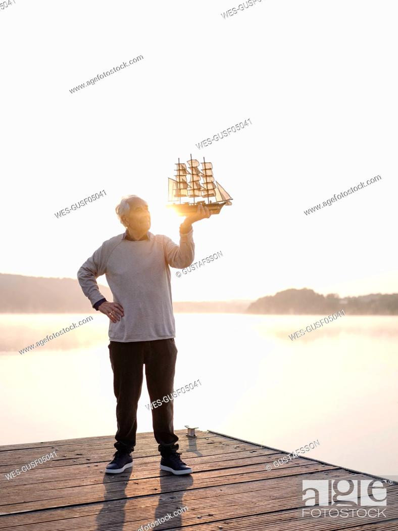Stock Photo: Senior man holding sailing ship while standing with hand on hip against lake.