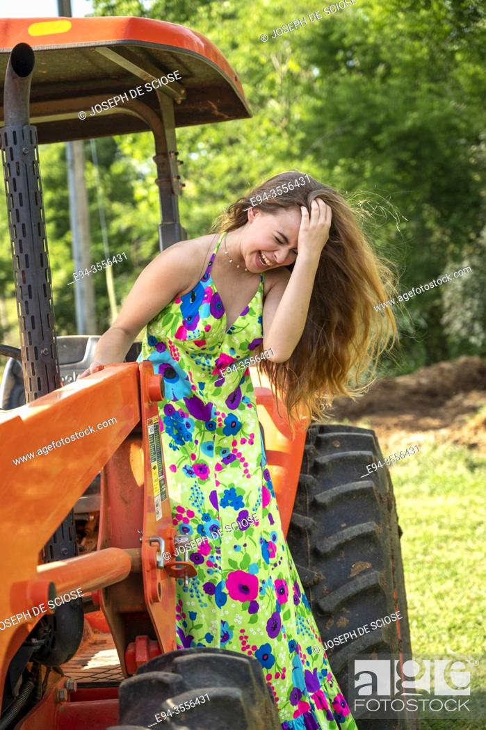Stock Photo: A laughing 14 year old brunette girl wearing a long colorful dress standing on a tractor.