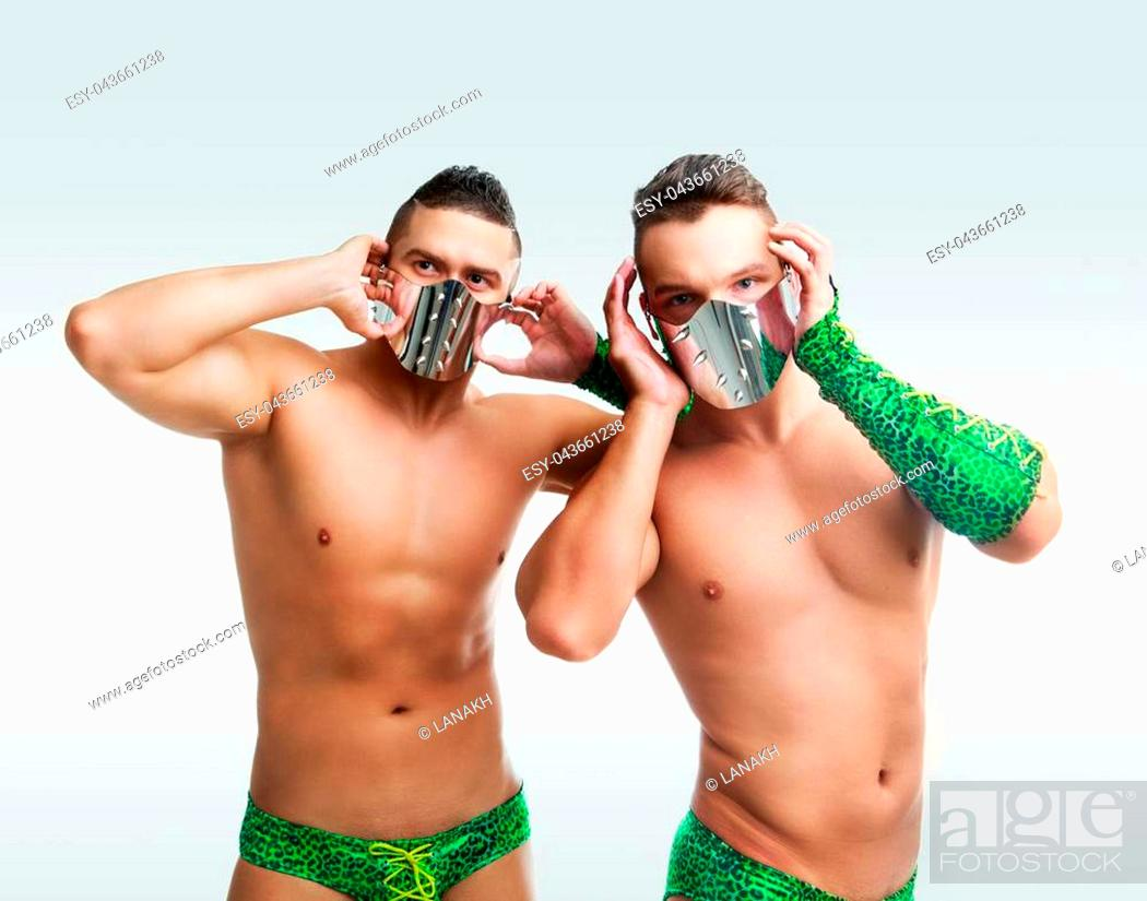 Stock Photo: striptease dancers wearing green costumes in the studio isolated against white background.