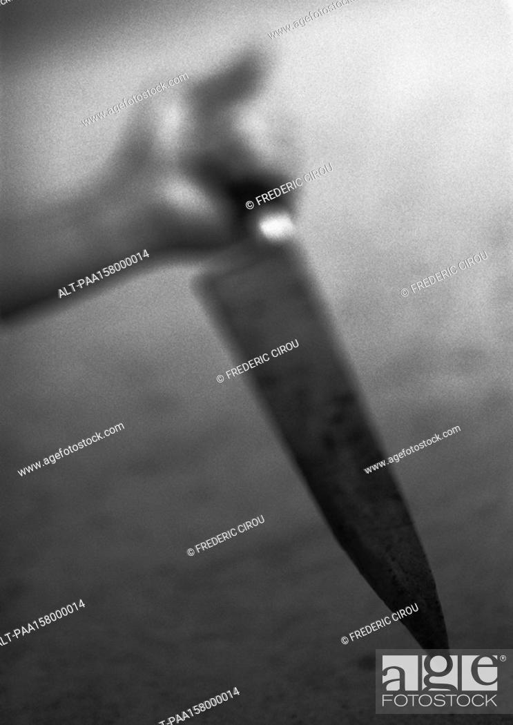 Stock Photo: Hand holding kitchen knife, blurred, b&w.