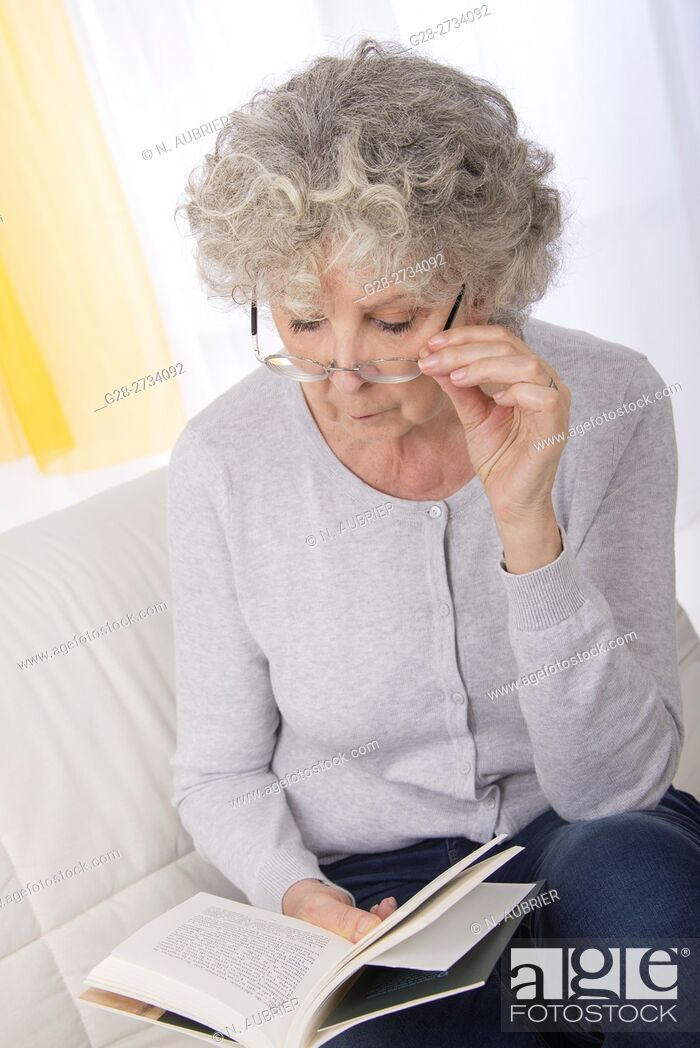 Stock Photo: Senior woman sitting on her sofa, peacefully reading a book, her spectacles on her nose.