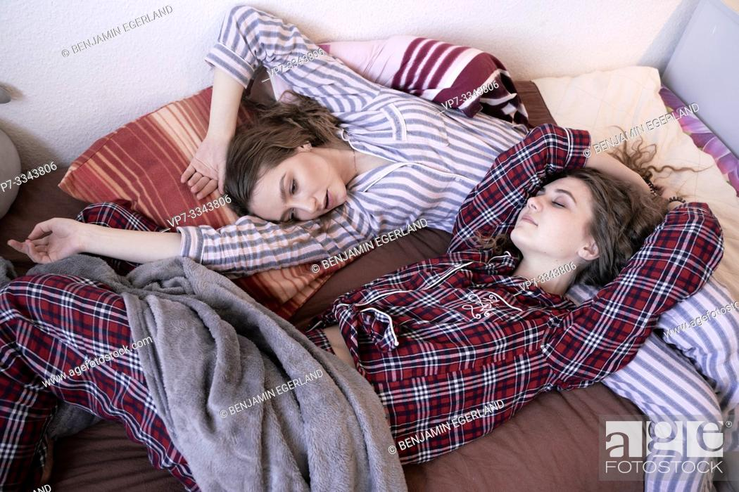 Stock Photo: two young women laying in bed together, wearing pyjamas.