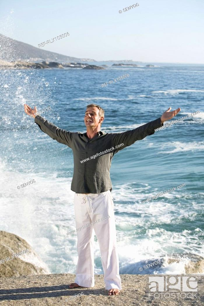 Stock Photo: Man standing on cliff with arms outstretched, smiling with waves in background.