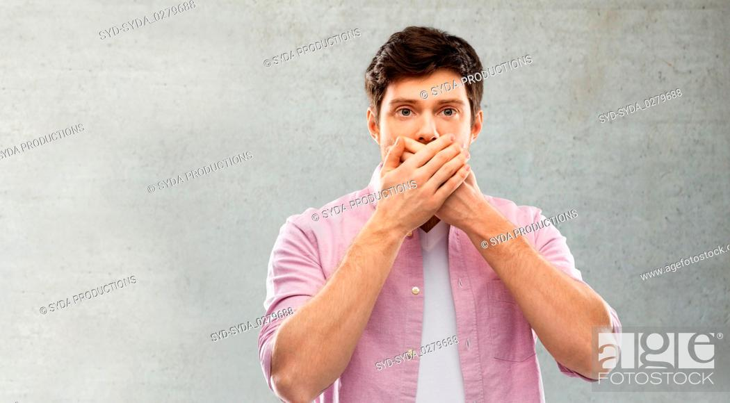 Photo de stock: shocked young man covering his mouth by hands.