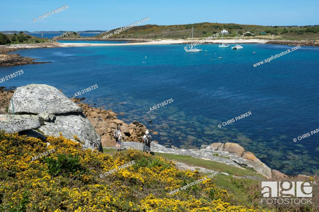 Stock Photo: Hikers On The Coastal Path Around St Agnes With The Island Of Gugh And The Sand Bar In The Distance, Isles Of Scilly, Cornwall, Uk, Europe.