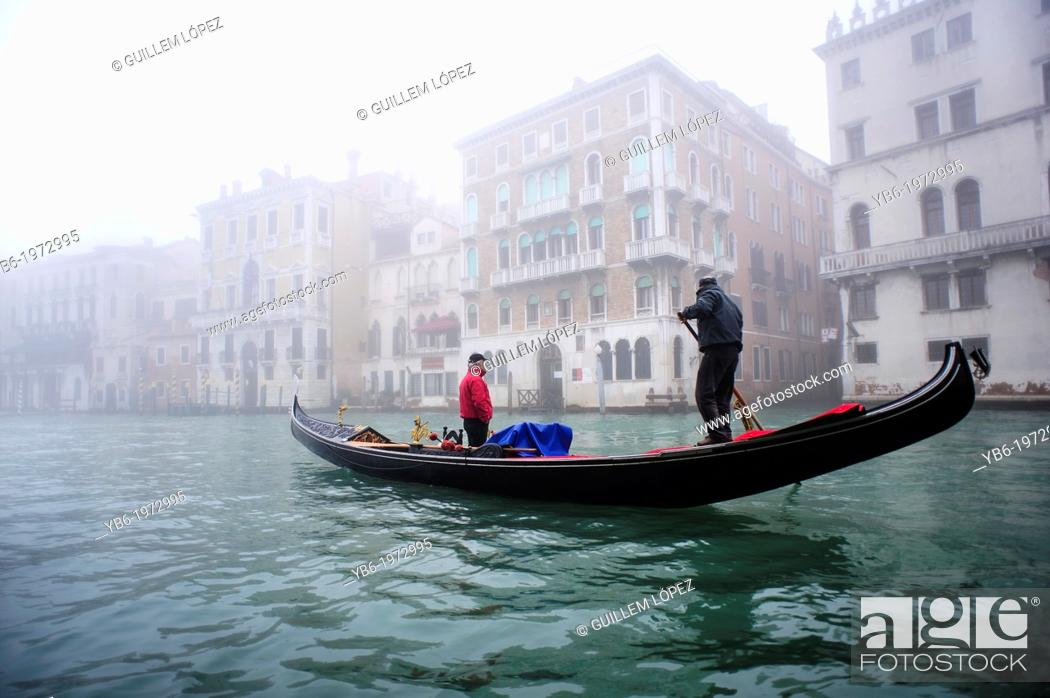 Stock Photo: A Gondola sailing along the Grand canal of Venice covered with thick fog, Italy.