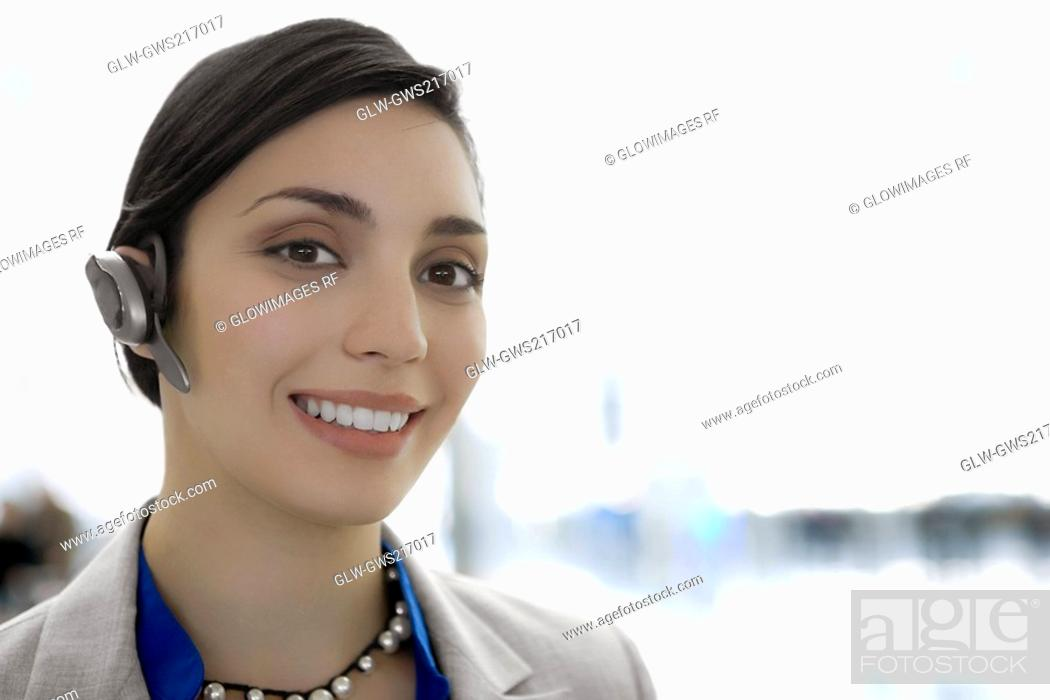 Stock Photo: Portrait of a businesswoman wearing a hands free device and smiling.