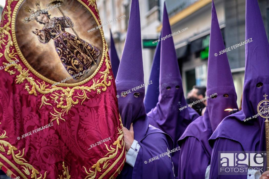 Stock Photo: Nazarenos participating in a religious procession, with the traditional robes and hoods and carrying a banner for their brotherhood during Semana Santa (Easter).