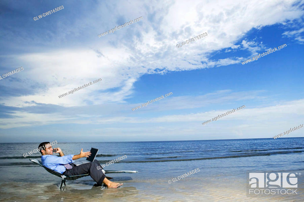 Stock Photo: Side profile of a young man sitting on the beach with a laptop.