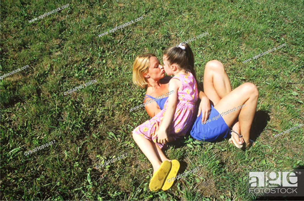 Stock Photo: High angle view of mother and daughter lying down on grass kissing.
