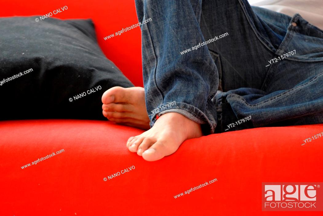 Stock Photo: Young man relaxing on a couch.
