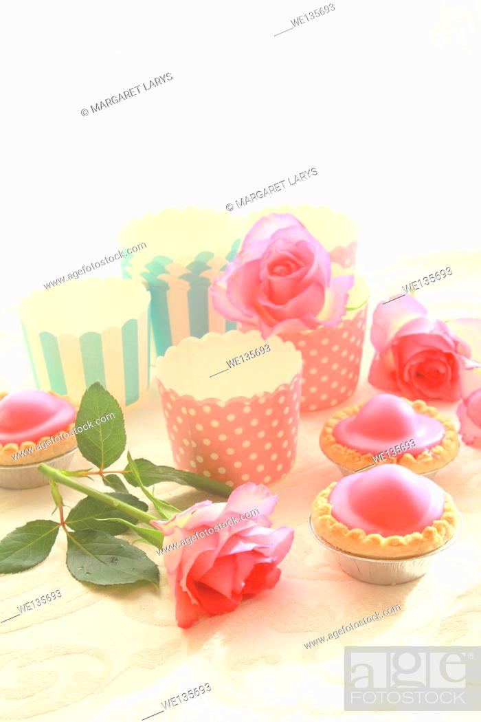 Stock Photo: Emepty round muffin cups and pink cakes.