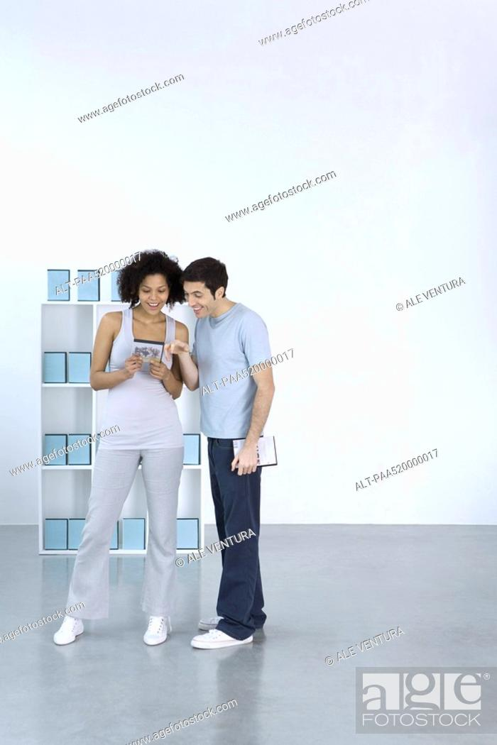 Stock Photo: Man and woman looking at DVD together, smiling.