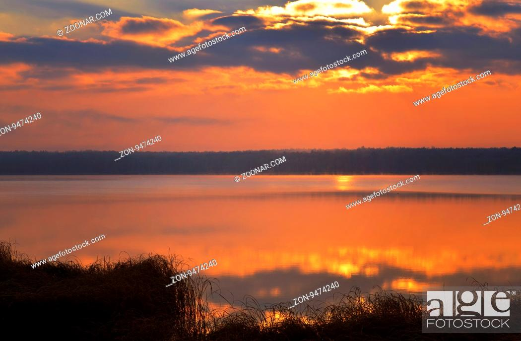 Stock Photo: Sunrise over the lake early in the morning with beautiful clouds.