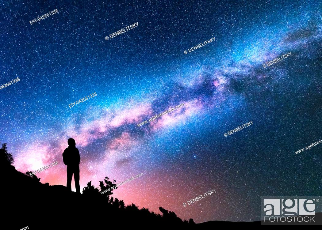 Stock Photo: Silhouette of man with backpack on the hill against colorful Milky Way at night. Space background. Landscape with man, bright milky way, sky with stars.