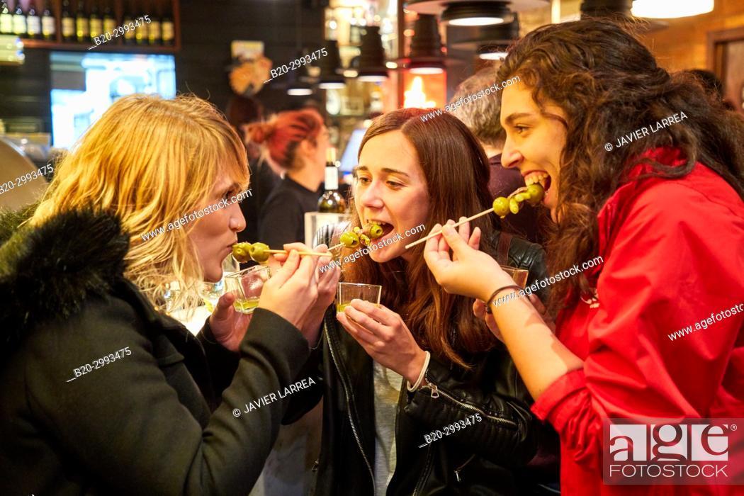 "Stock Photo: Guide with tourists eating a """"Gilda"""", Typical Pintxo from Donostia, Old Town, Donostia, San Sebastian, Gipuzkoa, Basque Country, Spain, Europe."
