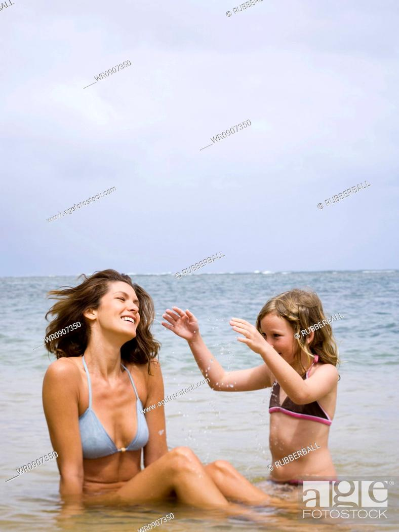 Stock Photo: Mother and her daughter sitting in water.