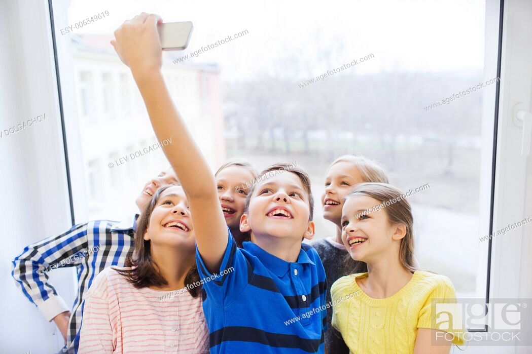 Stock Photo: education, elementary school, drinks, children and people concept - group of school kids taking selfie with smartphone in corridor.