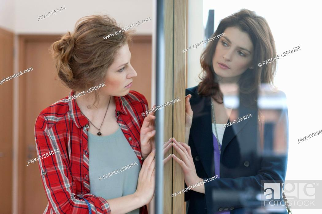 Stock Photo: Two female friends standing back to back against a door.