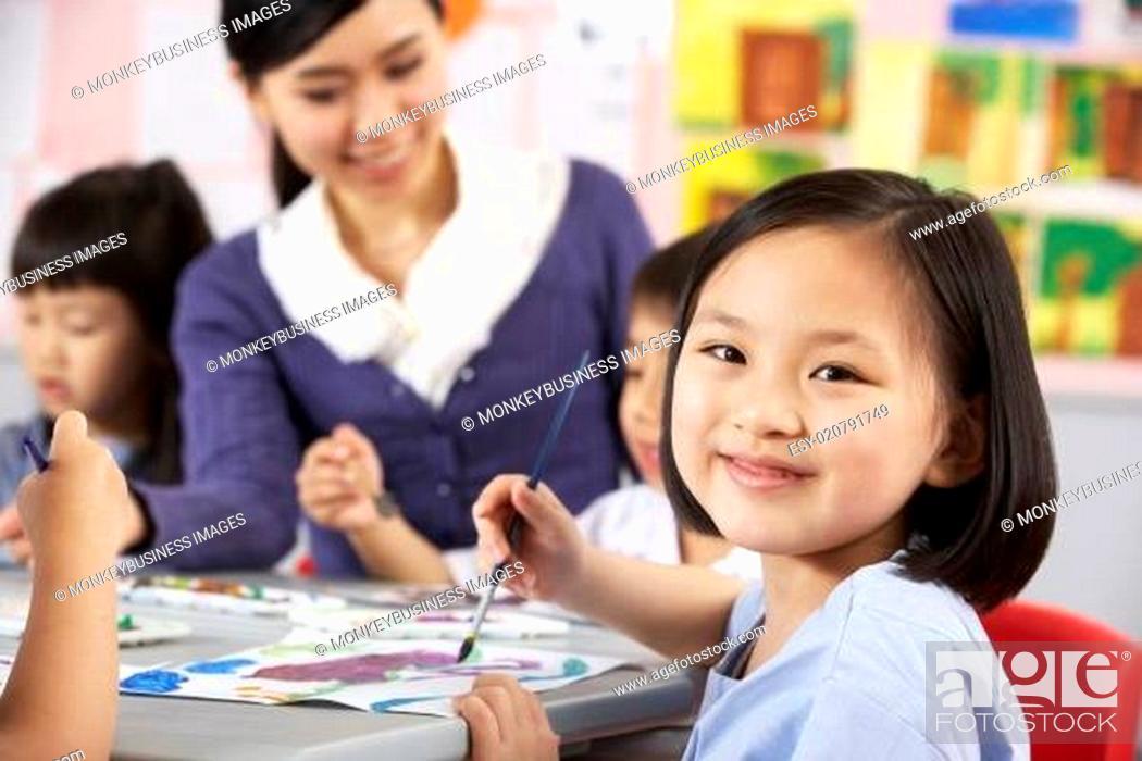 Stock Photo: Female Pupil Enjoying Art Class In Chinese School Classroom.