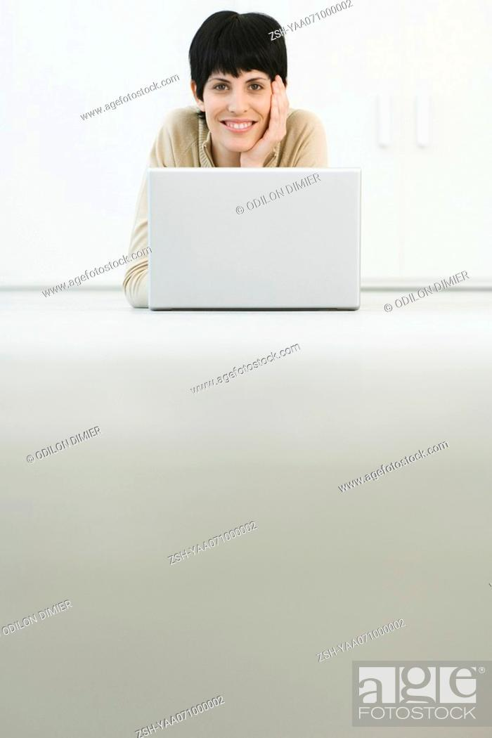 Stock Photo: Woman lying on stomach, smiling over laptop at camera, low angle view.