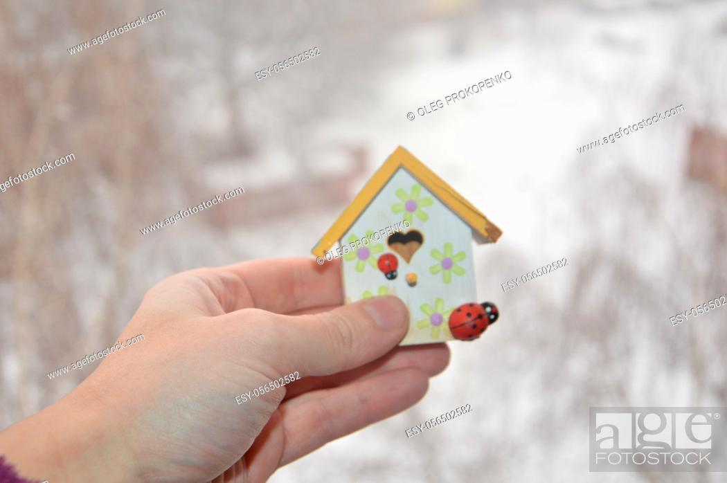 Stock Photo: A small house stands on a window frame against the background of the winter.