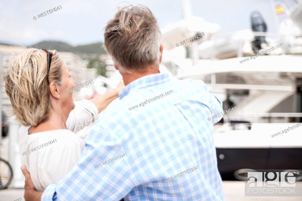 Stock Photo: Spain, Senior couple pointing to boat at harbour.