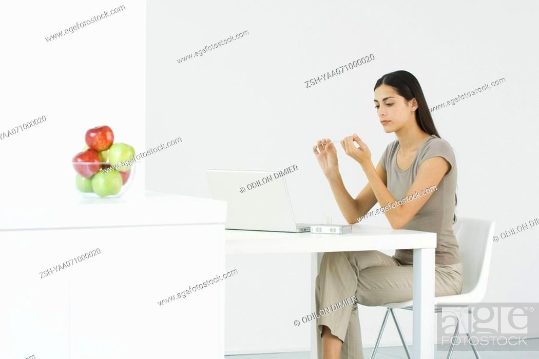 Stock Photo: Woman sitting at table in front of laptop computer, filing nails.