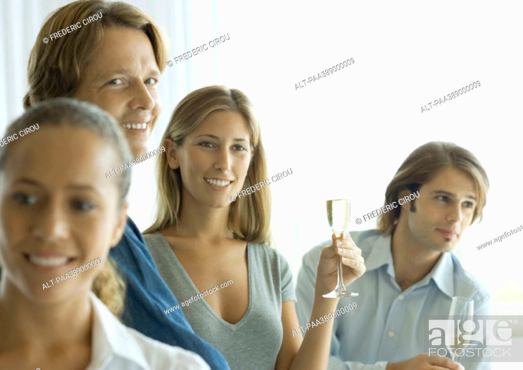 Stock Photo: Young adults drinking champagne at cocktail party.