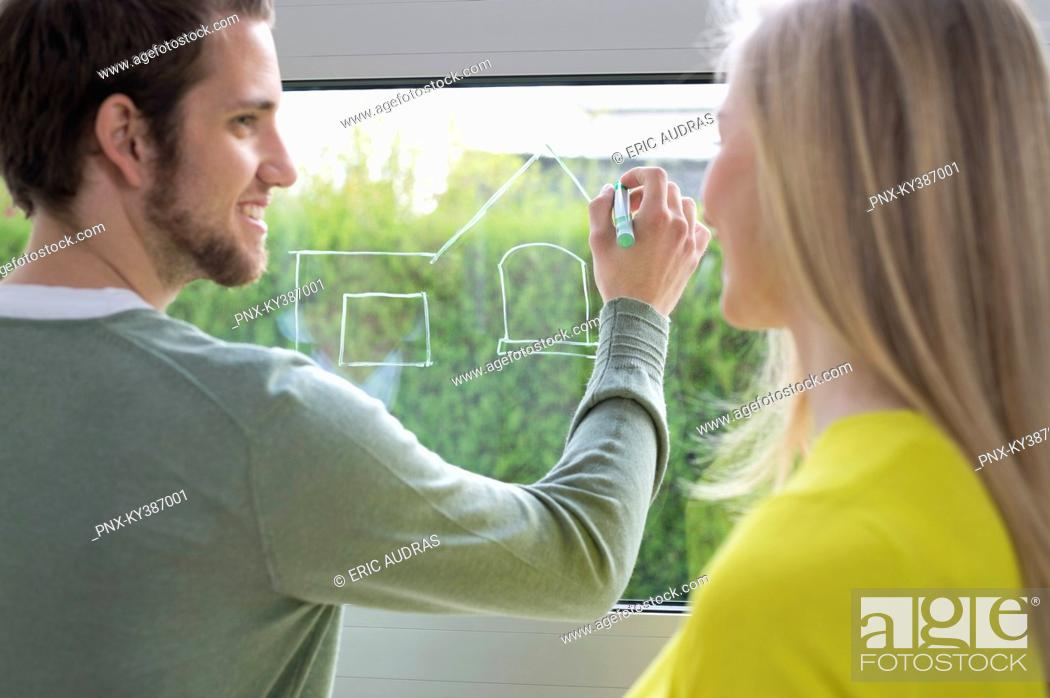 Stock Photo: Woman looking at an architect drawing a design on the window glass.