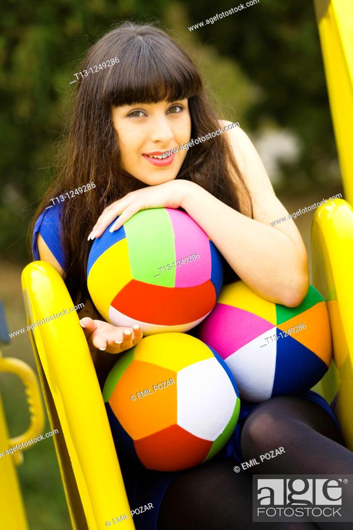 Stock Photo: Playful on top of the slide young woman with colorful balls.