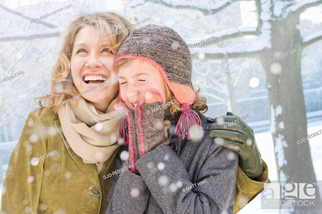 Stock Photo: Snow falling on smiling mother and daughter.