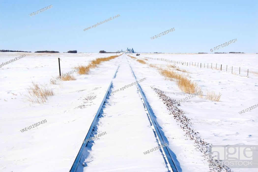 Stock Photo: Railroad tracks in snow covered rural landscape.