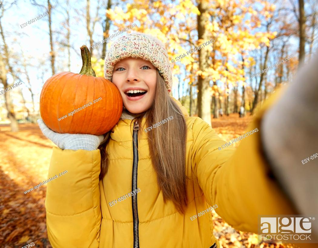 Stock Photo: girl with pumpkin taking selfie at autumn park.