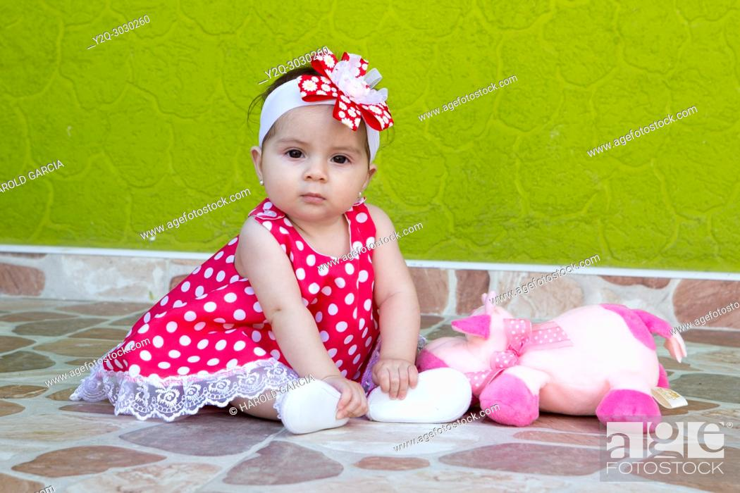 Imagen: little girl in a red and white polka-dot dress posing for the camera.