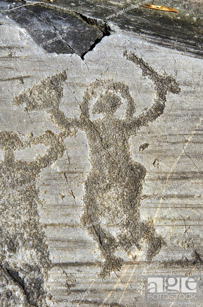 Stock Photo: Petroglyph, rock carving, of a warrior wearing a helmet and carrying a sword and shield. Carved by the ancient Camuni people in the iron age between 1000-1600.