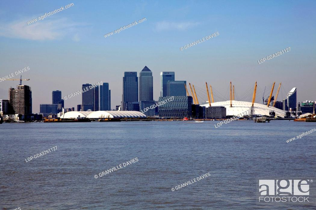 Imagen: England, London, Greenwich Peninsula. Canary Wharf skyscrapers and the O2 formerly the Millennium Dome viewed from the River Thames.