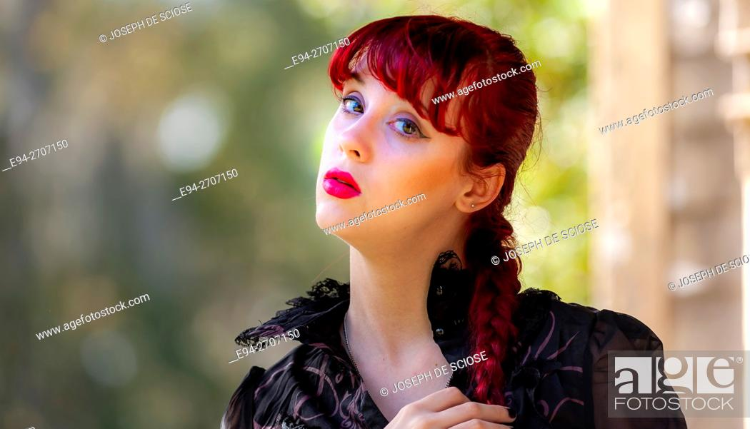 Stock Photo: A pretty 23 year old red headed woman looking at the camera, outdoors.