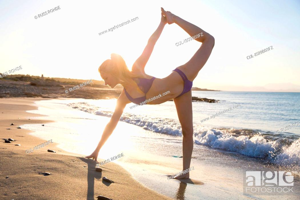 Stock Photo: Young woman on beach, in yoga position.