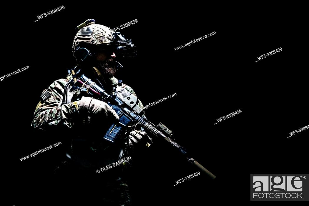 Stock Photo: Bearded soldier in Combat Uniforms with weapon, plate carrier and combat helmet are on. Studio shot, dark background.
